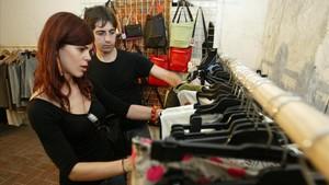 Dos personas repasan un probador de ropa en Barcelona.