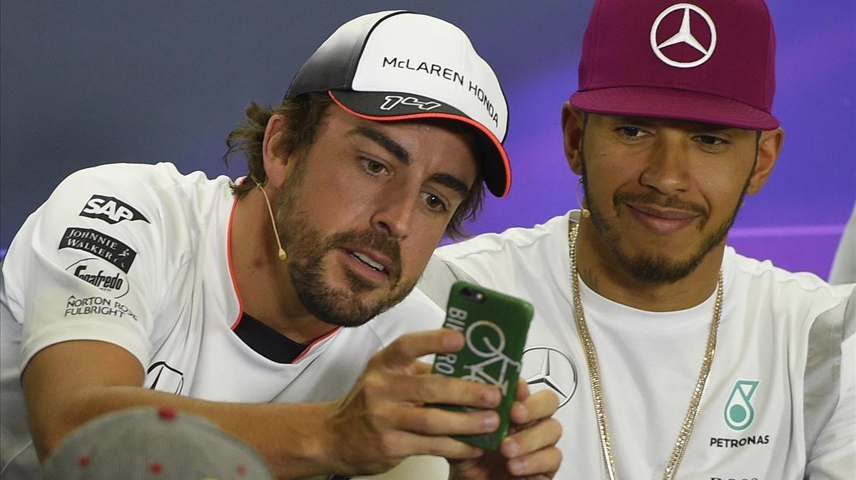 Alonso toma una fotografía con su móvil junto a Hamilton en Montmeló.