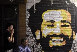 Un aficionado egipcio muestra su preocupación en El Cairo tras lesionarse Salah junto a una pintura del delantero.
