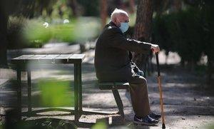 Un anciano con mascarilla, en un parque de Madrid, este viernes.