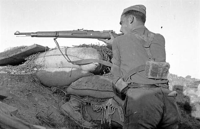 Soldado republicano disparando un fusil en el frente, durante la guerra civil.