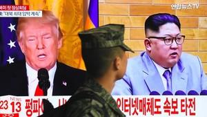 Un soldado surcoreano pasa ante un televisor que muestra las imágenes de Trump y Kim Jong-Un, en Seúl.
