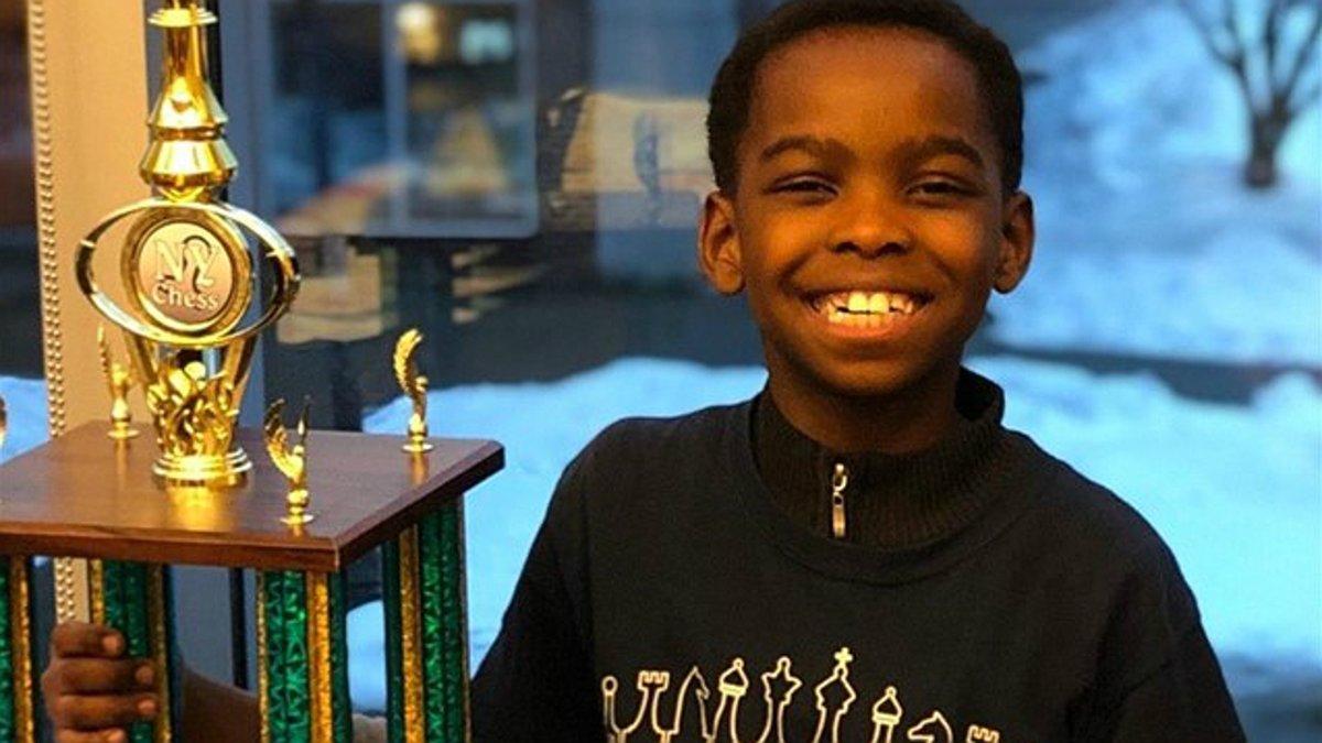 Tanitoluwa Adewumi, con el trofeo que le acredita como campeón escolar de ajedrez de Nueva York.