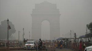 Turistas visitan la Puerta de la India bajo una fuerte niebla de polución en Nueva Deli.