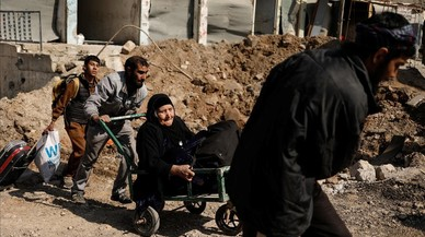 Una dona gran és arrossegada en un carret pels familiars en la fugida de la ciutat de Mossul (Iraq).