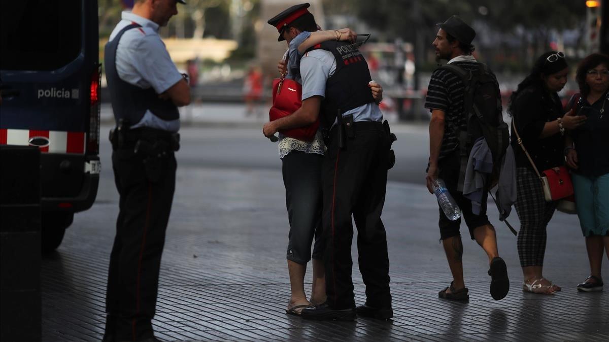 Una mujer abraza a un Mosso d'Esquadra tras visitar el memorial a las víctimas del atentado de Las Ramblas.