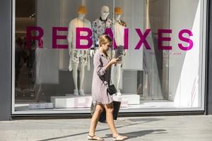 Una mujer mira su móvil mientras pasa delante de una tienda en rebajas.