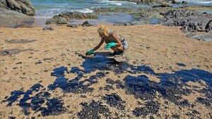 Una voluntaria recoge restos de crudo en la arena de una playa cerca del centro turístico de Oporto de Busca Vida en Lauro de Freitas, estado de Bahía.