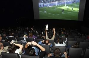 Aficionados siguiendo un partido de fútbol televisado en un cine madrileño.
