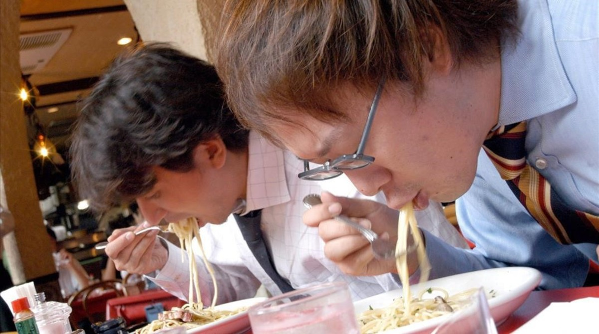Dos hombres comen en un restaurante.