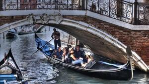 Unos turistas pasean en góndola por Venecia.