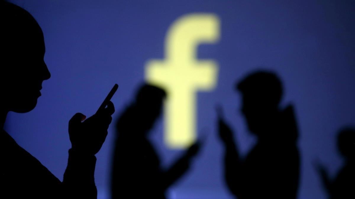 Unos usuarios de Facebook, ante el logotipo de la red social.