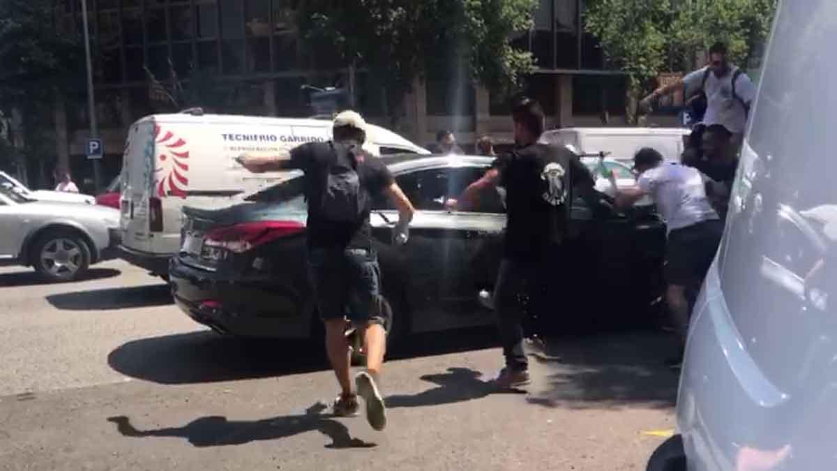 Manifestantes durante la huelga de taxis en Barcelona atacan un coche de Cabify
