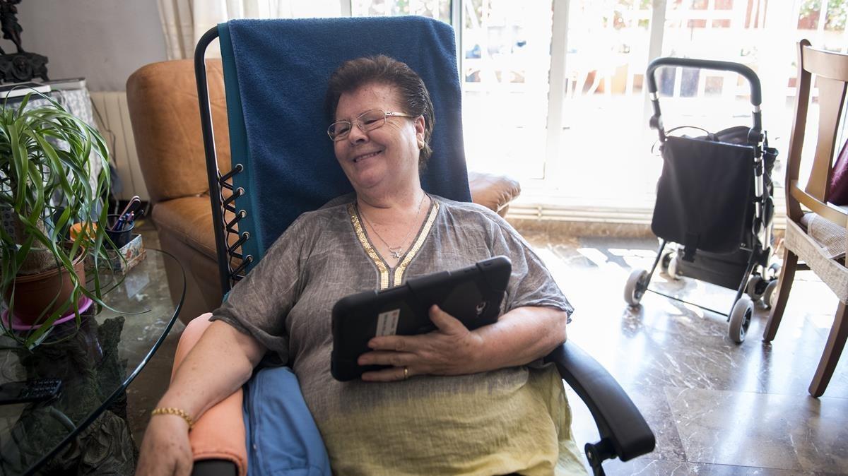 Neus Gutiérrez en su casa de Barcelona, el jueves con la tableta en la mano.