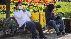 Dos repartidores de comida a domicilio protegidos con mascarillas, en un momento de descanso en Valencia.