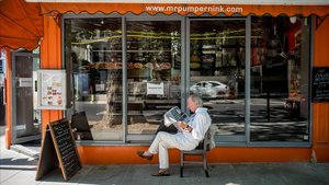 Un hombre lee un diario en la terraza de un restaurante.