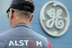 Un trabajador de Alstom frente al logotipo de GE, en abril del 2014.