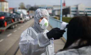 Un agente mide la temperatura a una mujer en un control por el coronavirus en la frontera entre Polonia y Alemania.
