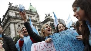 Centenares de personas contrarias a la ley del aborto se manifiestan en el exterior del Senado en Buenos Aires.