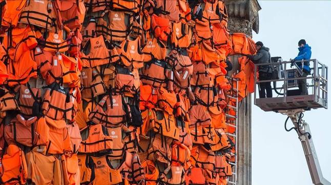 Asistentes del artista Ai Weiwei colocan chalecos salvavidas en la Kinzerthaus de Berlín, en recuerdo de los refugiados.