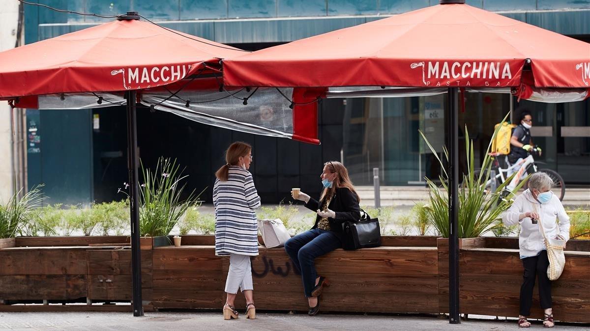 Varias personas toman café en una terraza cerrada de Barcelona, en mayo.