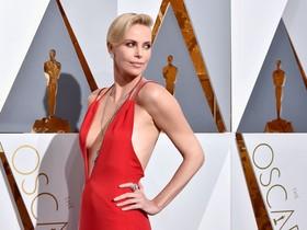 Charlize Theron, con un Dior rojo, a su llegada a la gala de los Oscar.