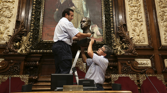 Dos operarios retiran el busto del rey Juan Carlos del salón de plenos del Ayuntamiento de Barcelona.