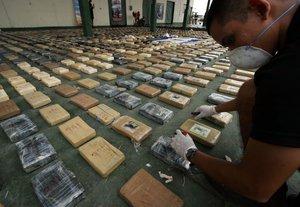 Un agente de la policia colombiana inspecciona un paquete con cocaina luego de realizarse un decomiso.