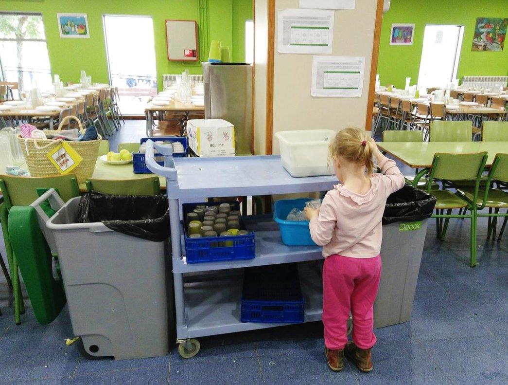 Un comedor escolar donde se ve una niña de espaldas eligiendo alimentos.