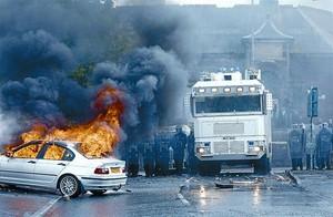 Un cotxe crema mentre els agents antiavalots observen l'escena al barri d'Ardoyne, a Belfast.