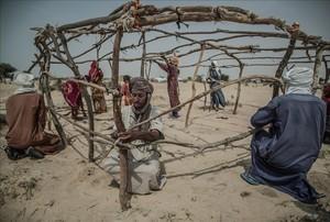 Un grupo de desplazados construye una cabaña en el asentamiento de Manara.