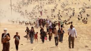 Desplazados yazidís huyen hacia la frontera siria, en los alrededores del monte Sinjar, ante el avance de las milicias del EI, el 10 de agosto del 2014.