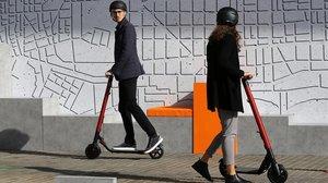 Dos usuarios de patinete eléctrico.