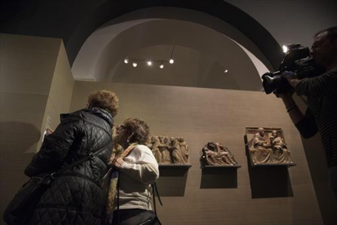 Dos visitantes observan algunas de las obras del monasterio de Villanueva de Sijena que custodia el Museu de Lleida.