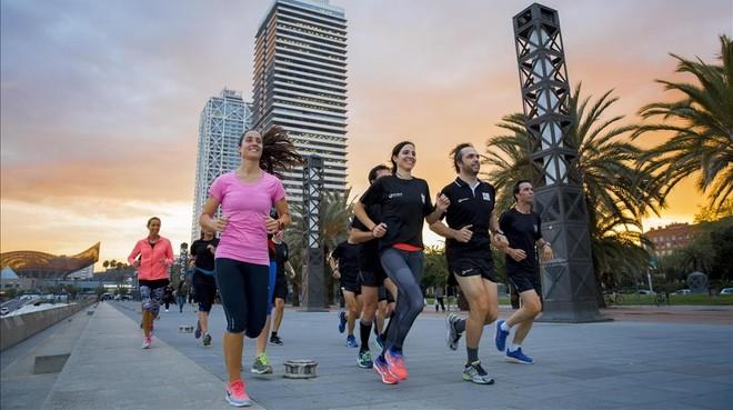 Sara Carmona (de rosa) y dos 'coaches' deBrisport,Fabrizio GravinayJosefina Toscano, guían al grupo de 'runners' 'deluxe' por el paseo marítimo.