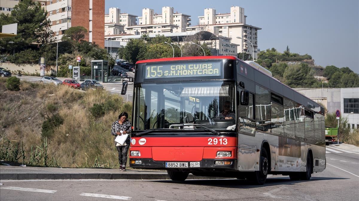 El 155, bus no articulado, con Ciutat Meridianacomo telón de fondo.