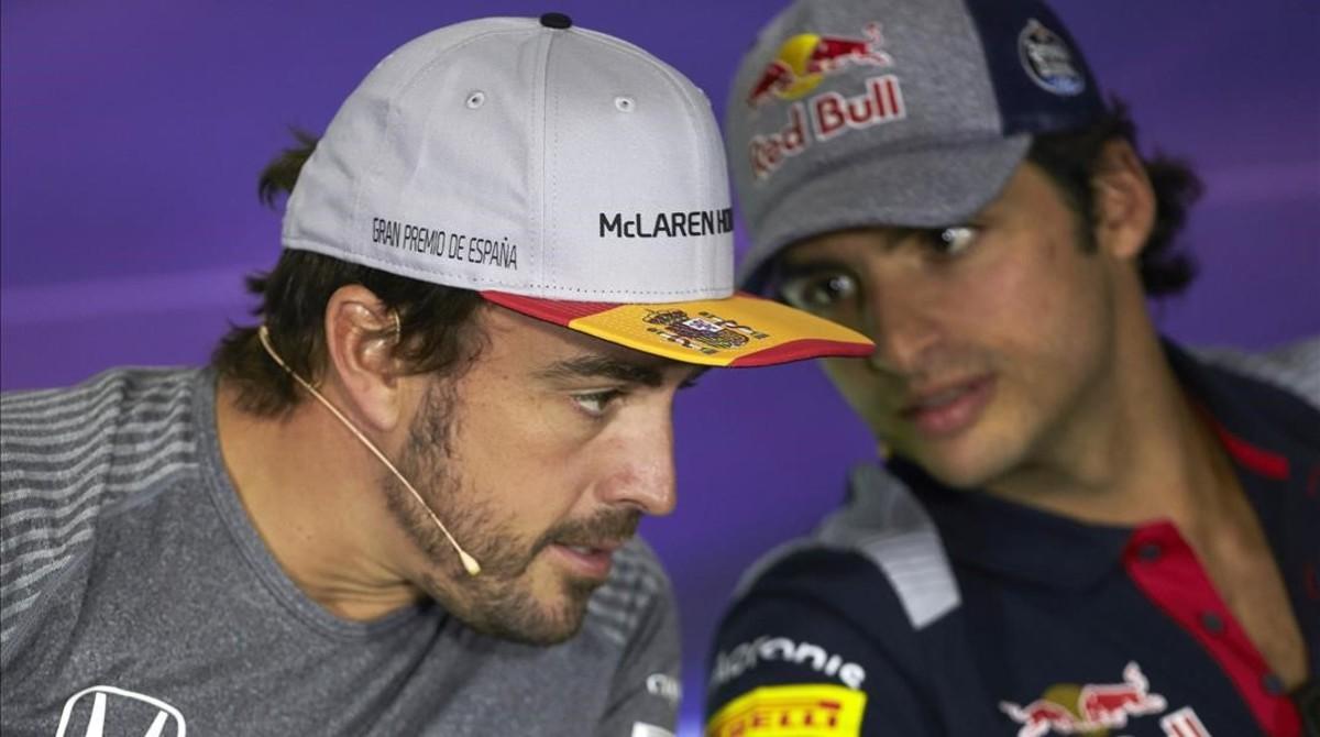 Fernando Alonso atiende a Carlos Sainz.