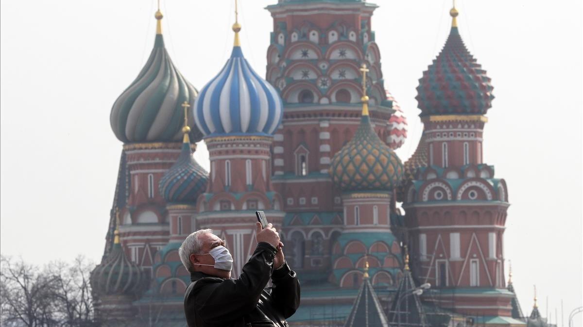 Un hombre hace fotos frente a la catedral de Vasily the Blessed en la Plaza Roja de Moscú