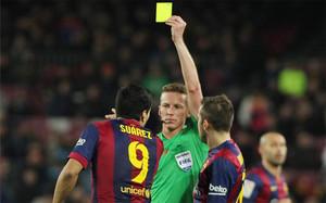 El colegiado canario Hernández Hernández mostrando una tarjeta a Luis Suárez.