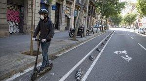 Un hombre circula en patinete por Consell de Cent, en Barcelona.