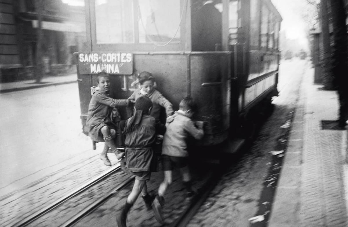 Unos niños se encaraman de manera peligrosa a un tranvía con paradas en los barrios de Sants, Les Corts y Marina, datada entre 1920 y 1939.