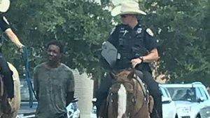 La imagen de la polémica: dos policías montados a caballo trasladan a un hombre negro atado con una cuerda, en Galveston (Texas).
