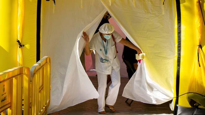 Máximo de contagios por coronavirus en España en un día: 1.772. En la foto, una sanitaria sale de una de las carpas instaladas para hacer pruebas PCR en Ripollet.