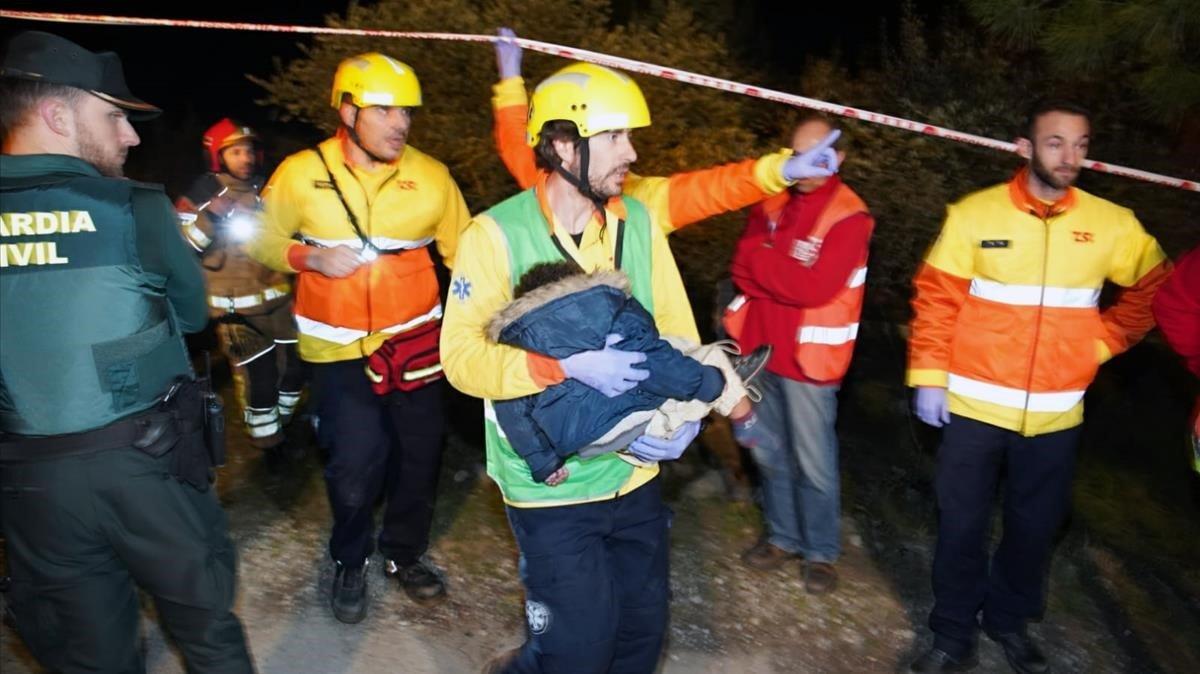 Miembros de Emergencias trasladan a un menor en brazos para ser atendido.