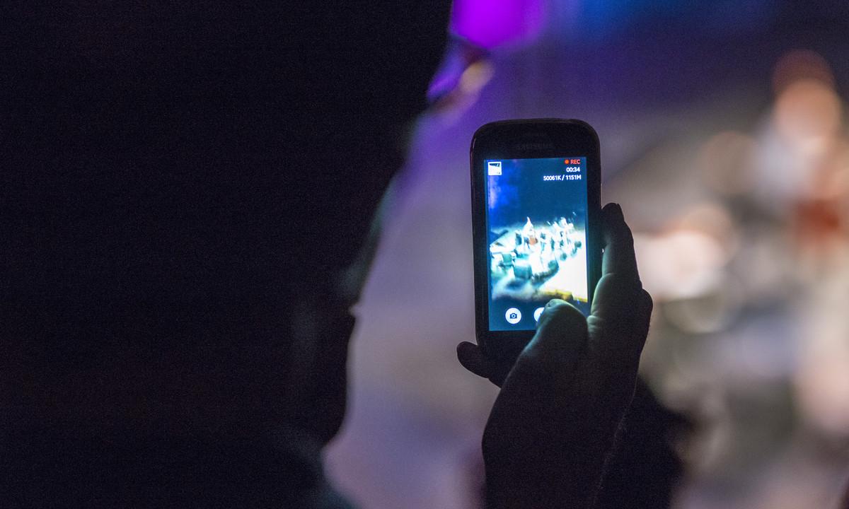 Un usuario utilizando su teléfono móvil durante la noche.