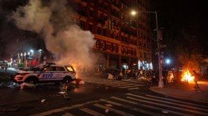 Un numeroso grupo de manifestantes observan cómo arde un coche de la policíaen Manhattan, este sábado 30 de mayo, durante las protestas por la muerte de George Floyd en Minneápolis.