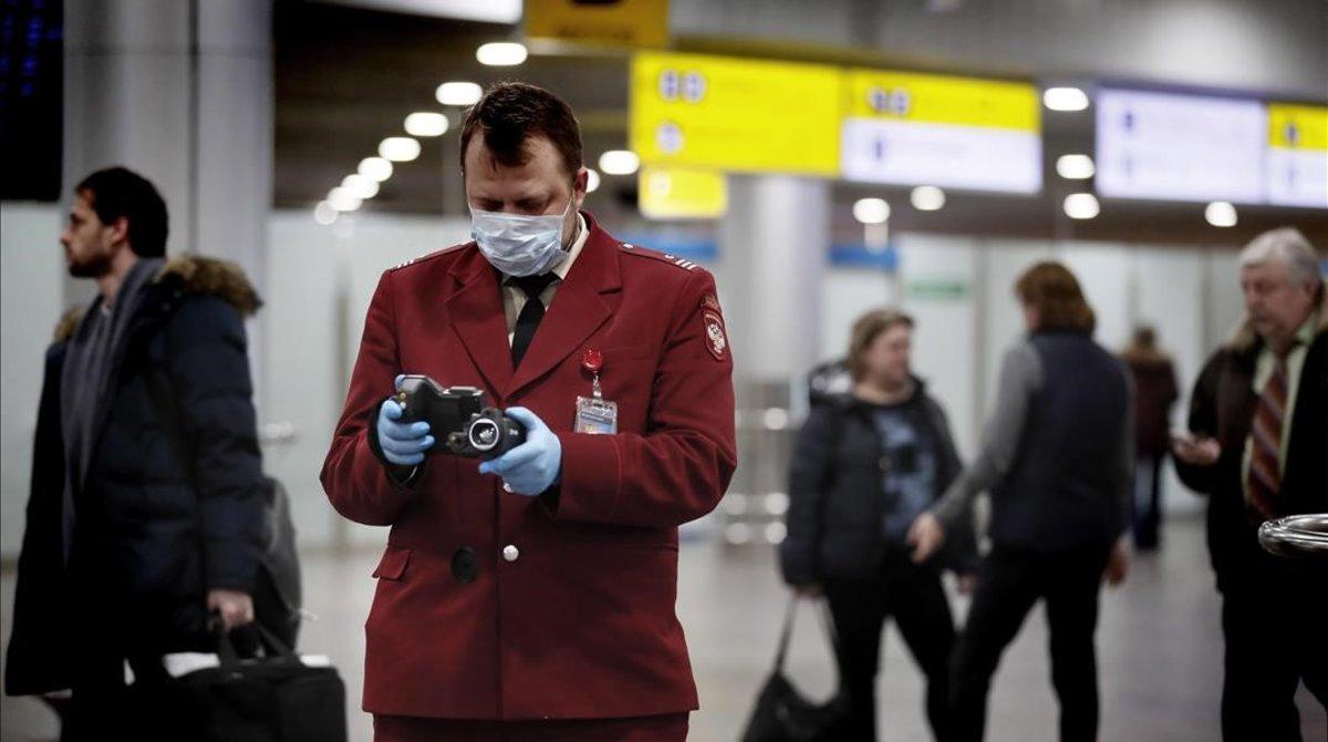 Un oficial de sanidad con un aparato para tomar la temperatura en el aeropuerto de Moscú.