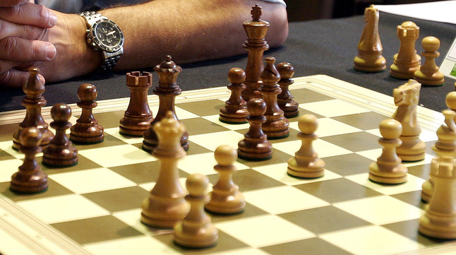 Un tablero de ajedrez y sus fichas.