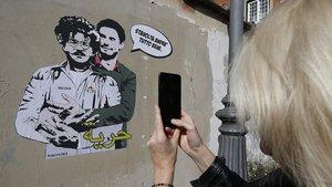 Una mujer toma una fotografía de un mural con las imágenes dePatrick George Zaki(izquierda) junto aGiulio Regeni, cerca de la embajada de Egipto en Roma.