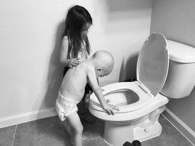 El pequeño Beckett vomita apoyado por su hermana, en una imagen que su madre, Kaitlin Burge, ha publicado en Facebook.